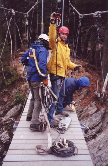 men tightening cables on suspension bridge